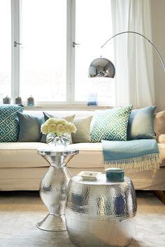 Gehämmertes Metall ist ein orientalischer Stil-Klassiker. Hier ersetzen zwei verschiedene Beistelltische den Couchtisch. Das lockert den Raum auf und das Material kommt auf den unterschiedlichen Formen perfekt zur Geltung!