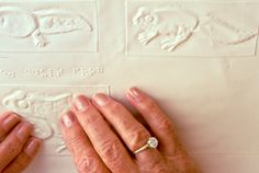 Close Up Of Hands Reading Braille: Tactile Graphics