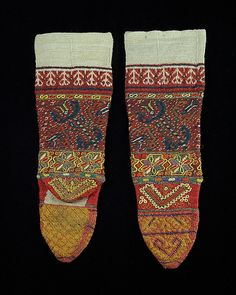 These socks display a skillful use of color,used in creating a multitude of floral,geometric and stylized goddess figure motifs.The use of embroidery creates an additional layer of visual interest and richness. Although identified as from the Macedonian town of Servia,which lies west of Mt. Olympus,as a result of the 1913 Partition,Servia in 2008 lies within the Kozani prefecture of Greece.