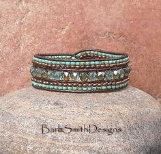 The Indian Princess in Verdigris  This enchanting cuff bracelet takes on beautiful shades of patina. It is done in 6mm fire-polished aqua Czech glass beads. The two outer rows are stitched in Copper Oxide Metal and Turquoise Opaque Picasso seed beads. This Indian Princess is adorned with a copper toned button, surrounded by two rows of seed beads and a Josephine Knot. The two feathers are finished with Copper Oxide beads. This bracelet is stitched on a Metallic Brown Indian leather cord…