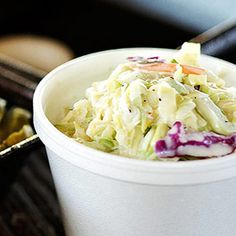 In a very large bowl combine cabbages and carrot. In a small bowl combine mayonnaise, sour cream, sugar, vinegar, mustard, salt and pepper; stir into cabbage mixture. Cover and chill at least 2 hours before serving.