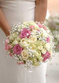 Wedding bouquet with button roses, freesias and gypsophilia: We made this sphere shaped wedding bouquet using bubblegum colours and incorporating button roses with slightly larger antique style roses. We softened the sphere with gypsophilia and freesias, which added a delicious fragrance.