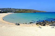 Porthmeor Beach in St Ives, Cornwall. The deep blue water is popular with surfers.  Portugal? | 12 Places You'd Never Believe Were In The U.K.