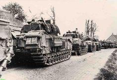 0210358 Coll. Chr. Warnar: Militairen bij zware Britse Churchill tanks op de Voordeldonk op weg naar Liessel. Op de achtergrond het huis van Lens  Berkers,  Driek van Kessel en Piet Berkers.   Graag verbeteren en/of aanvullen.