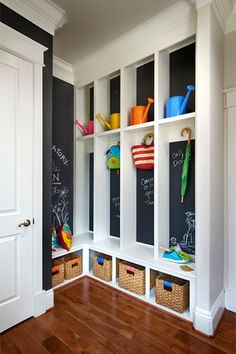 An all-white mudroom gets a dose of personality with colorful accessories and creative scribbles. Chalkboard paint keeps organizing easy in this Parkwood Homes-designed corner created for a family's changing needs.