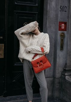 Fashion blogger Beatrice Gutu wearing JW anderson red bag with houndstooth pants and heavy chunky knit outfit ideas