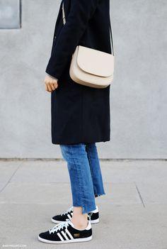 Adidas sneakers, jeans, a black coat, and a Mansur Gavriel bag.