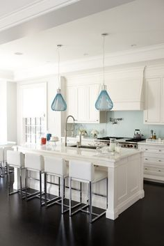 White kitchen with dark wood floors and blue backsplash. Kitchen with blue pendant lights over white kitchen island with marble countertops