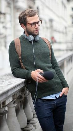 green woolen jumper, over pale blue shirt, and dark blue jeans, casual clothes for men, worn by young man with glasses, with brown backpack, and grey headphones