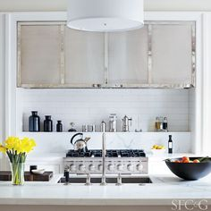 Bright and white kitchen with chrome shelves and appliances and daffodils