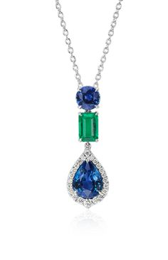 Truly stunning, this pendant features a vibrant emerald and showcases a beautiful pear-shaped sapphire surrounded by brilliant pavé-set diamonds
