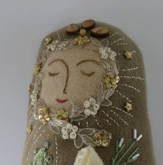 An original handmade doll approximately 12 inches tall. Her body is a beautiful piece of hand dyed wool fabric with appliques and embellished with beads