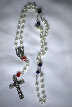 This is a glass bead Rosary, created from 6mm White Pearls, and 8mm Red and Blue alternating Our Father glass beads. Description from etsy.com. I searched for this on bing.com/images