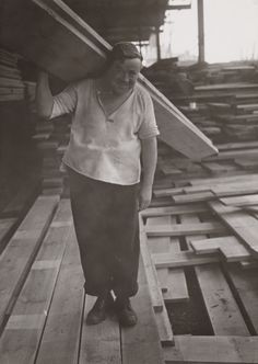 Stevedores on the London docks -      Description:  A photograph of stevedores on the London docks, taken in August 1937 by Harold Tomlin for the Daily Herald.     The photograph shows a man carrying a plank during the heatwave of 1937. Stevedores were dock labourers responsible for loading and unloading ships.