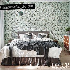 O papel de parede com estampa floral traz charme e personalidade ao dormitório. Aconchegante, o décor combina tons de verde, cinza e branco que contrastam com o móvel e o piso em madeira aparente. Já as luminárias de parede e mesa concedem toques em estilo industrial ao cômodo.