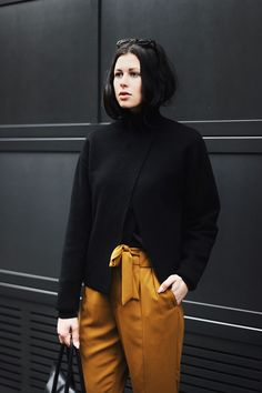 Elisa from the Fashion- and Lifestyleblog www.schwarzersamt.com is wearing a black turtle neck sweater from H&M Studio Collection, yellow /cutty loose fit pants, business shoes from ZARA and a bag from HIELEVEN. It's a minimal und clean allblack blogger look with yellow accents.