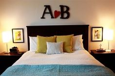 Spouses' initials above the bed with a heart in between + wedding/occasion photos above the nightstands