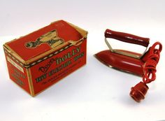Dover Dolly Toy Electric # 68 Red. This is a toy - not electric. Dover made full size products, and this is a child size. The cord looks like a heavy cotton braided cord with a huge red wood knob 'plug'. The iron top is red with a red wood handle. The iron itself is fairly heavy (especially for a child!), metal, with a shiny ironing surface.