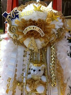 Senior gold and white homecoming mum with gold bear in a swing.