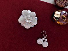 Compoziția florală este confecționată din sidef și perle de cultură.
