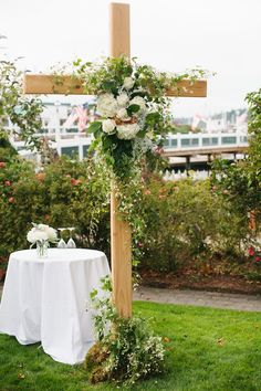 Wedding ceremony cross decorated with flowers and vines for a Roche Harbor wedding.  Wedding Planning & Design: Perfectly Posh Events. Photo: Lucid Captures Photography. Flowers: Robin's Nest.