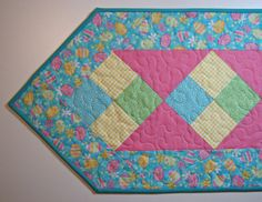 Pretty pastel Easter eggs border this quilted table runner, ready to display on your table at Easter! Measuring approximately 14.25 inches wide and 39.5 inches long point to point, this Spring table runner features 4 scrappy patchwork blocks in charming yellow checks, turquoise dots and mint green swirls running down the center of the runner, with a pink pin dot background, all coordinating nicely with the outer Easter egg border. All fabrics are cotton. Layered with Warm and Natural cotton…
