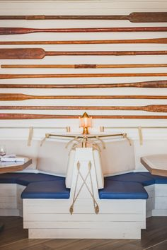 PETERMAX Co — The Yacht Club. Nautical Theme Inspired. The space consists of a light balance of white and warmth | Ship Lighting fixtures found throughout the space. #lightingfixtures | Dining Area with booth seating | Boat Paddle Design #ropedecor