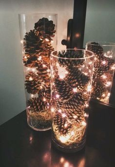 pine cones and fairy lights in hurricane glasses