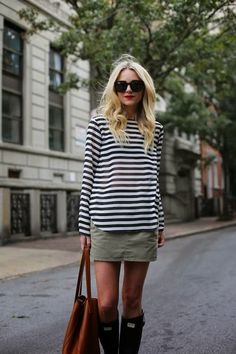 an olive green mini skirt, a striped long sleeve, black rain boots