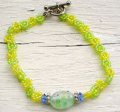 """SOLD. Green and Yellow Daises bracelet features Murano bead, Swarovsky beads, Sterling Silver beads and seed beads. 7"""""""
