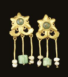 A PAIR OF ROMAN GOLD, EMERALD AND PEARL EARRINGS Circa 3rd Century A.D. Each with a six-pointed rosette with small openwork loops between the petals, centered by an emerald bead threaded on to a central wire, a crossbar below of stylized serpent heads, with three suspension loops on the reverse, each with a length of twisted wire, two threaded with two pearls, the central one threaded with an emerald bead, the reverse with an S-shaped earwire 1½ in. (3.8 cm.) long (2)