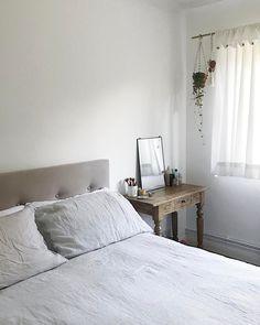 Rustic grey bedlinen, vintage desk, white walls, macrame plant hanger, bedroom.