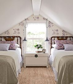 Floral wallpaper highlights a peaked roof and compliments the vibrantly hued pillow shams.