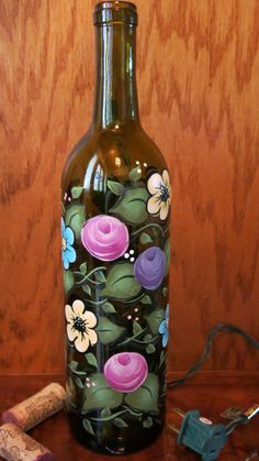 This recycled green wine bottle has been painted with pink, yellow, lavender, blue flowers and vines and leaves. Glass paints were used and baked Wine Bottle Art, Painted Wine Bottles, Lighted Wine Bottles, Diy Bottle, Painted Wine Glasses, Bottle Lights, Wine Bottle Crafts, Glass Bottle, Pebeo Porcelaine 150
