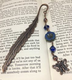 This copper feather shaped bookmark has been decorated with blue and brown Czech glass beads. A pretty butterfly charm adds the finishing touch. Organza Gift Bags, Czech Glass Beads, Bookmarks, Feather, Copper, Butterfly, Pendant Necklace, Metal, Gifts