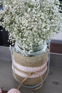 Mason Jar Centerpieces - wrapped in burlap and lace and filled with baby's breath. --Simple and beautiful!