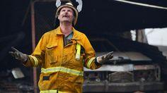 Zaterdag 3 januari 2015: Een medewerker van de vrijwillige brandweer in Adelaide reageert verheugd op het vallen van de eerste regen na lange droogte in het gebied in het zuiden van Australië, dat geteisterd wordt door natuurbranden.