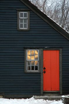 New England Cottage Detail.orange/red door on antique blue/black house; window directly adjacent to door.