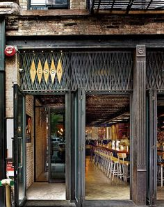 Cold-rolled blackened steel security grating brings industrial appeal to Tessa restaurant by Bates Masi + Architects (via Interior Design Magazine) Decoration Restaurant, Design Bar Restaurant, Modern Restaurant, Chinese Restaurant, Commercial Design, Commercial Interiors, Design Innovation, Shop Facade, Exterior Signage