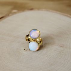 Gold Double Opalite Cabochon Adjustable Ring  This ring is a perfect everyday ring. The ring is made from an adjustable gold plated base. The ring hold two single 12mm opalite stone cabochons. The bezel and stones together are 14mm.  Each ring is adjustable so it will fit most ring sizes.  You will receive one ring at random.  The photos show multiple rings. You will receive one ring.  Please keep in mind that each piece is handmade and may differ form the pictures…
