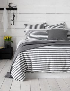 Our Coastal Stripe Charcoal bed linen is the perfect companion for your coastal inspired bedroom. Contrasting white and grey stripes, paired with crisp white sheets and coastal wooden floorboards. #greycoastalbedrooms