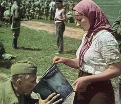 A Russian woman gives a German POW a drink of water near Kiev, uncredited