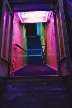 "image description: city stairwell leading down decorated with a ""watch your step"" sign and pink, purple, red, and green neon lights Vaporwave, Tableaux D'inspiration, The Wicked The Divine, Neon Noir, Catty Noir, Neon Aesthetic, Violet Aesthetic, Nocturne, Neon Lighting"