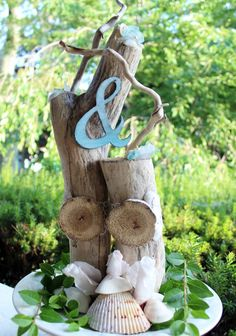 Love the idea of driftwood center pieces https://www.etsy.com/ca/listing/200959652/one-of-a-kind-beach-wedding-centerpiece