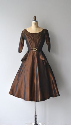 Vintage 1950s metallic copper taffeta party dress with scoop neckline, 3/4 sleeves, contoured stitched flaps on the bodice, fitted waist, matching