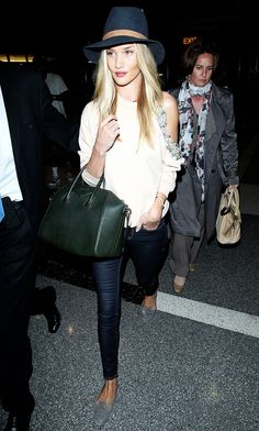 Rosie Huntington-Whiteley in a chic fedora, skinny jeans, and grey loafers for her flight