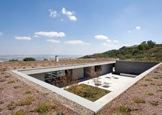 Sunken below the crest of a hill in southern Italy, this concrete home and its outdoor pool were designed to be almost imperceivable from the road above.