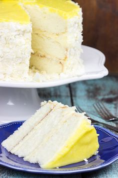 Decadent coconut flakes...sweet vanilla buttercream...tart lemon curd.  One slice of this Lemon Coconut Cake will whisk you away to a warm Caribbean island! | @spicedblog