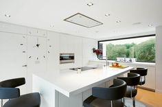 kitchen - cuisine blanche ilôt fauteuil cuir noir faux plafond spots noir et blanc horloge baie