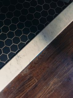 Black Hex tile Marble threshold- to wood floor -- Powder to kitchen transition